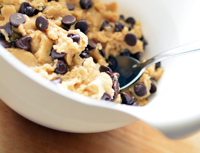 Raw cookie dough in a white mixing bowl with spoon